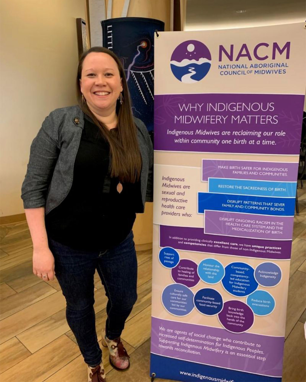 NACM Co‑Chair Claire Dion Fletcher with a banner produced for NACM by Inter Pares.